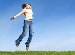 Woman leaping on high pasture